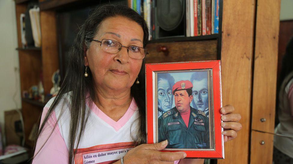 Teresa holds up a painting of President Chávez