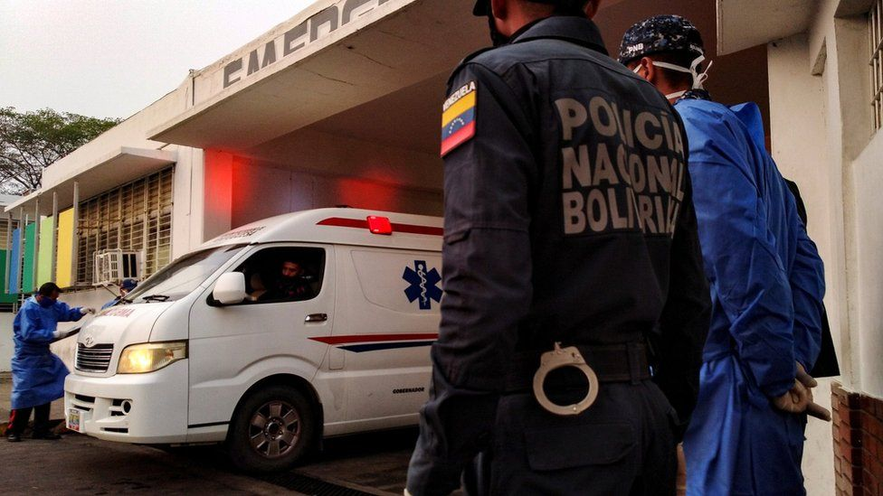 Healthcare workers and members of the Bolivarian national police watch as an ambulance arrives with prisoners outside a hospital after a riot erupted inside a prison in Guanare, Venezuela May 1, 2020.