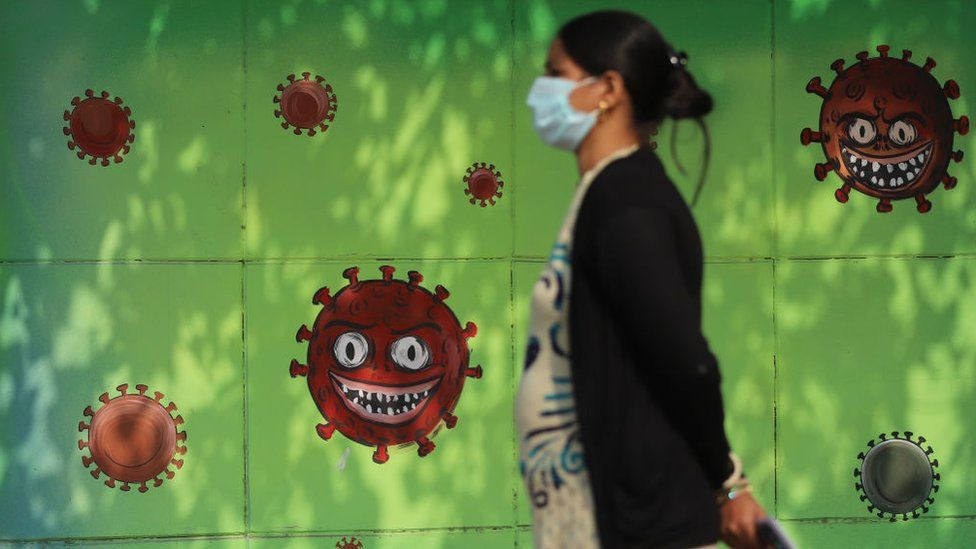 Woman wearing a facemask as a preventive measure against the Covid-19 coronavirus walks past a mural in New Delhi,