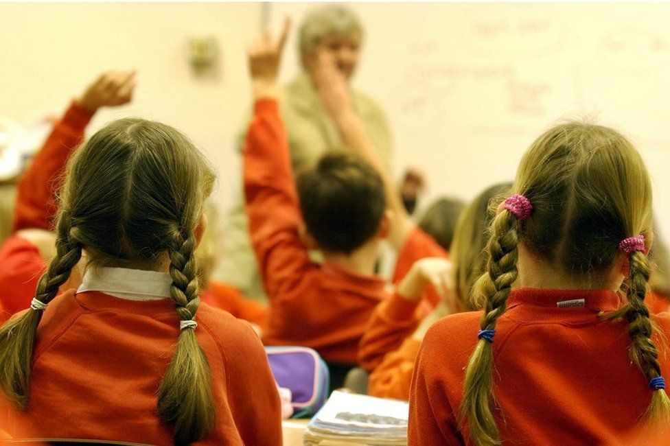 Children in a classroom, some with hands up