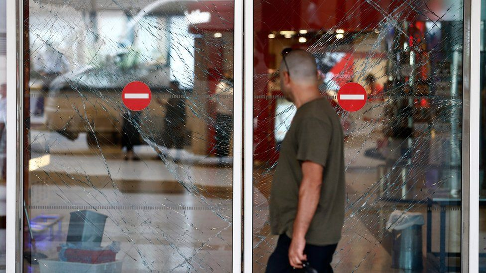 A person walks in front of broken window gates after multiple attacks at Ataturk international airport in Istanbul, Turkey, on 29 June