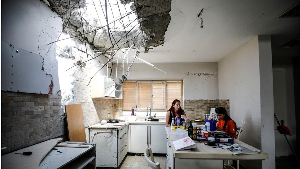 Members of the Vaizel family sit in the kitchen of their house, which was damaged after it was hit by a rocket launched from the Gaza Strip, in Ashkelon, Israel (20 May 2021)