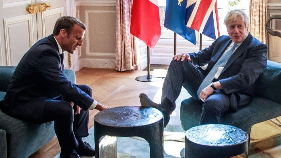 Mr Johnson with his foot on the table at a meeting with Mr Macron last month