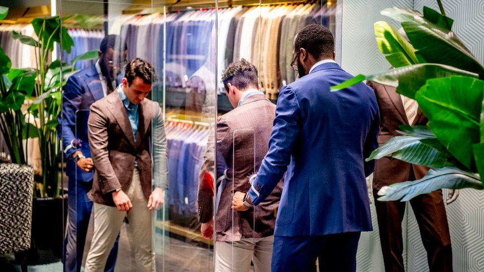 A tailor at Suit-supply in the Netherlands pins a suit on a customer through plexiglass