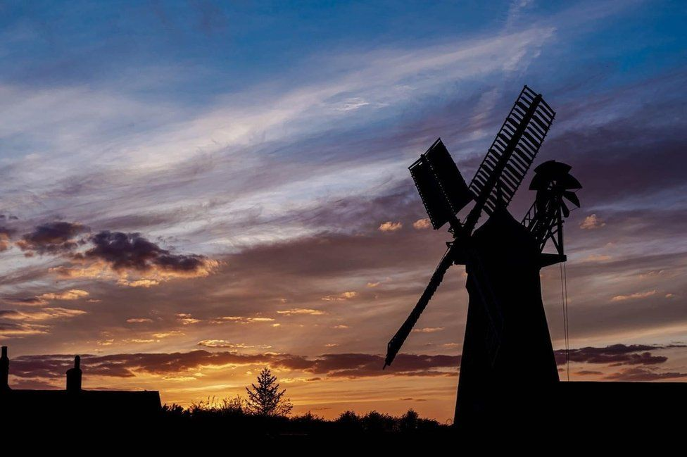 A windmill silhouette at sunset