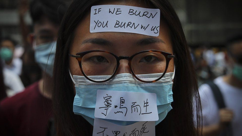 Masked protesters march in the street as they take part in a rally held to show opposition to an anti-mask law meant to deter anti-government protesters,