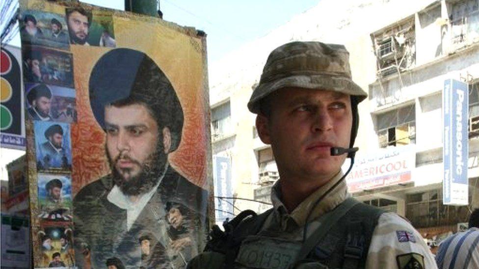 British soldier next to portrait of Moqtada al-Sadr in Basra, 2005