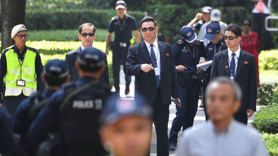 North Korean security personnel (C, wearing sunglasses) keep watch outside the St. Regis hotel, where North Korean leader Kim Jong Un is staying