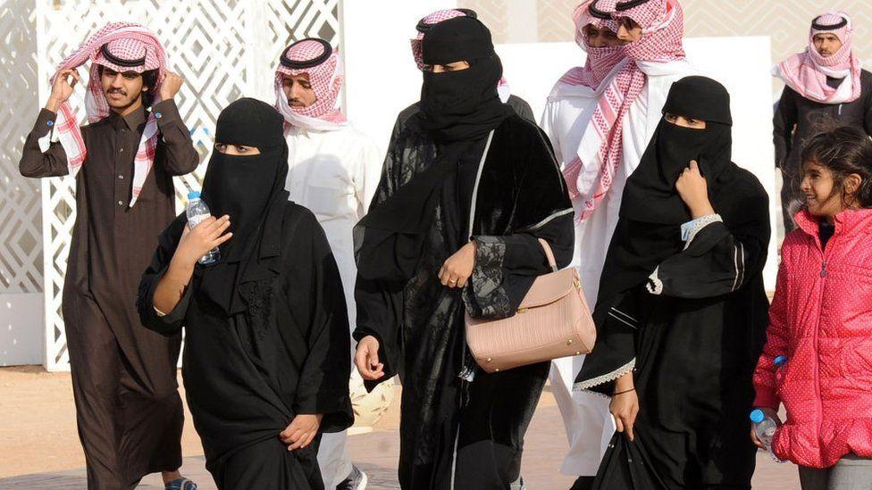 Saudi women in abayas and niqabs
