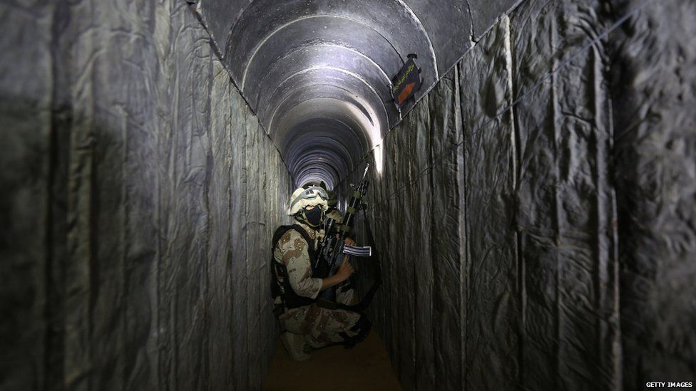Al Quds Brigade member crouches in a tunnel