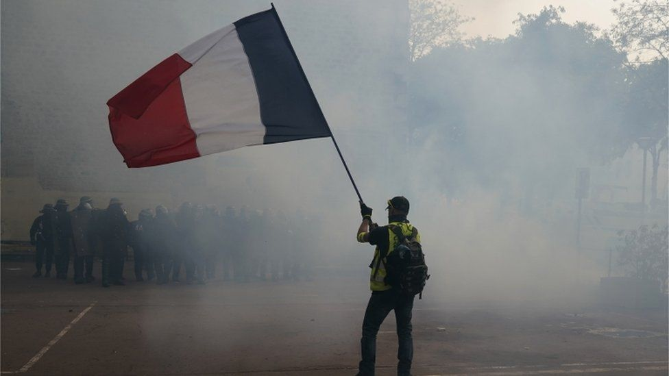 A protester holding a French flag in front of riot police in Paris