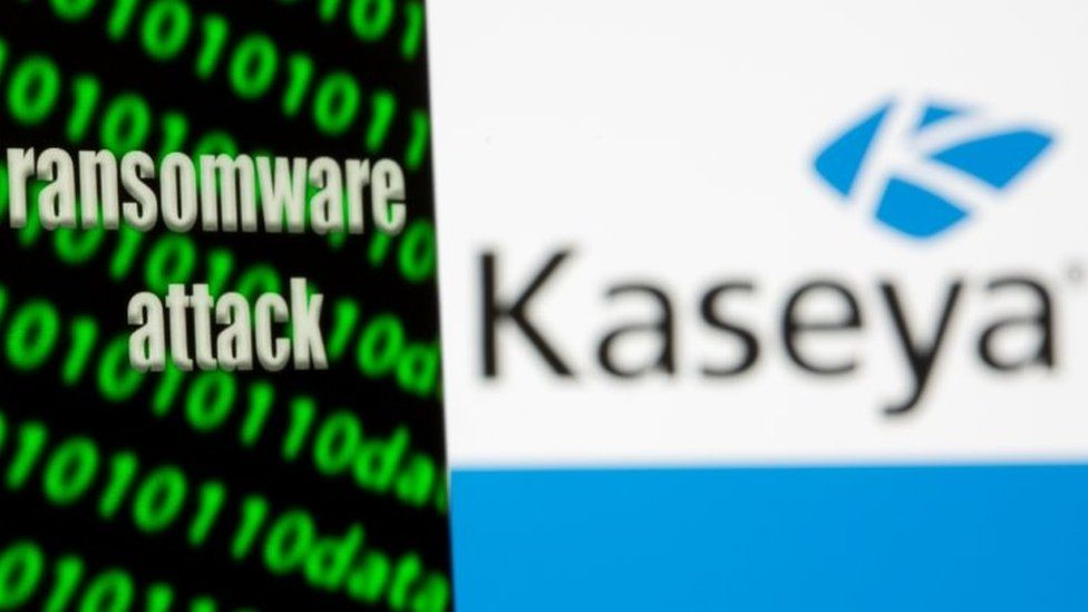 """A smartphone with the words """"Ransomware attack"""" and binary code is seen in front of the Kaseya logo in this illustration taken"""