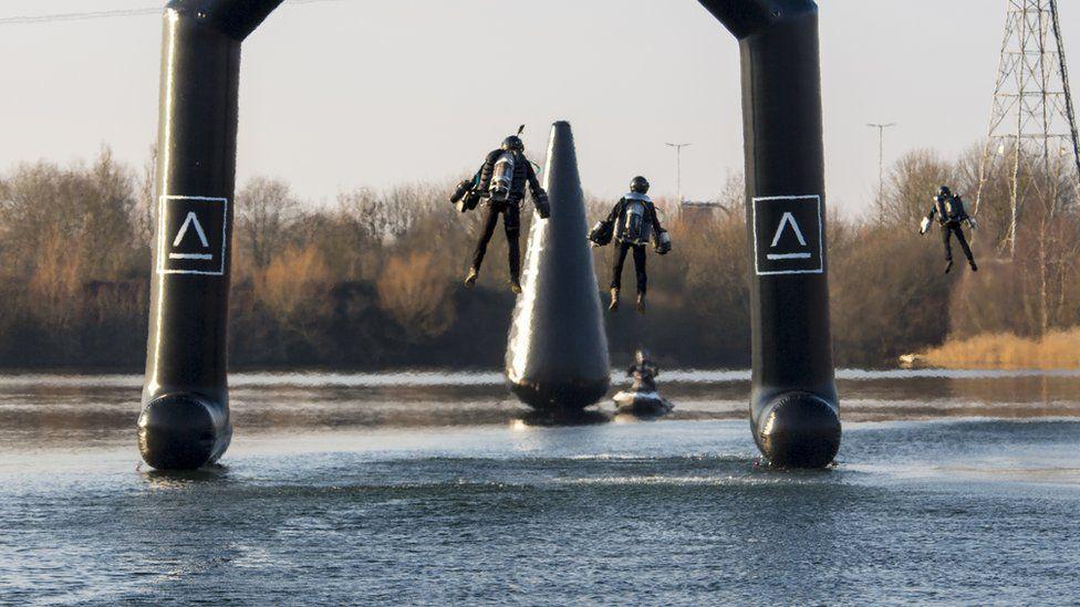 Three people wearing Gravity Industries jetpacks