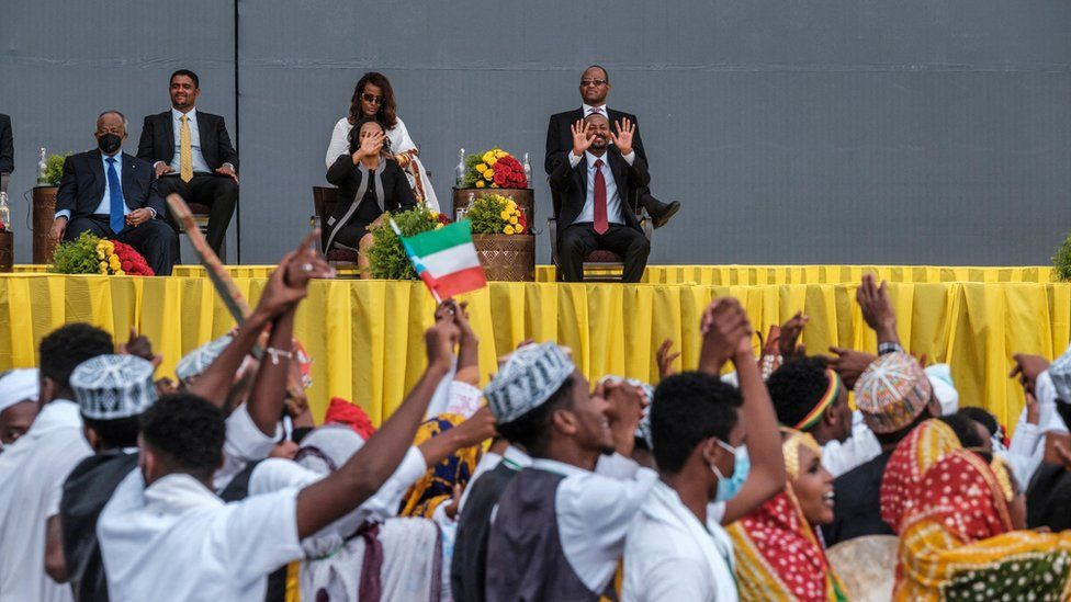 Ethiopia's newly sworn in Prime Minister waving to a crowd of people dressed in traditional clothing. One person is waving an Ethiopia flag. Abiy Ahmed is on an elevated stage with yellow draping. He is also accompanied with other people on the stage.