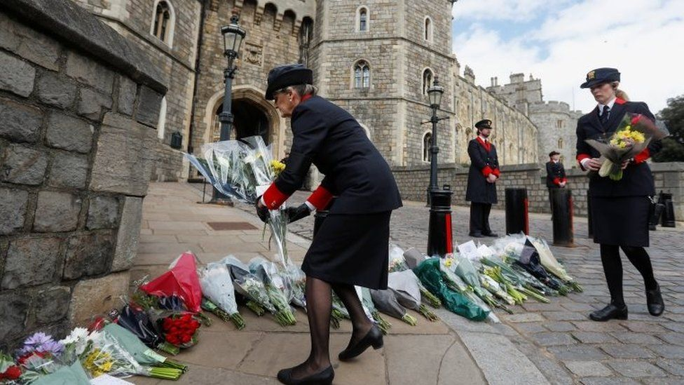 Windsor Castle wardens move flowers which were placed by members of the public outside Windsor Castle