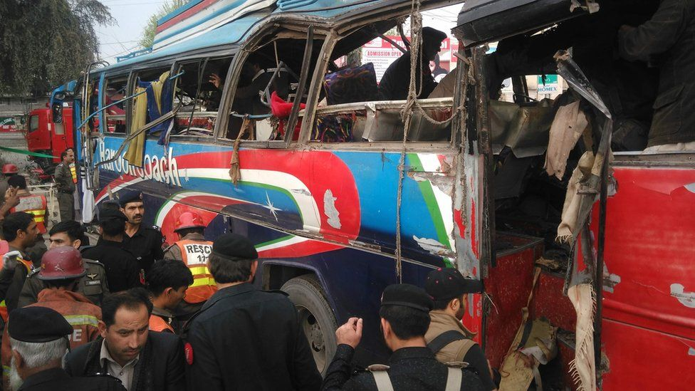Pakistani police officials search a damaged bus after bomb blast in Peshawar