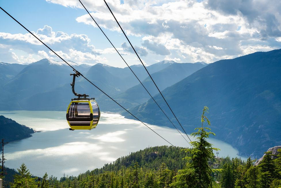 A shot shows a cable car move down towards a stunning lake at the base of rolling green mountains carpeted thickly with pine trees