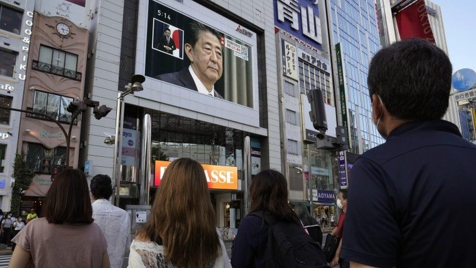 People watch a television announcement on Abe's resignation