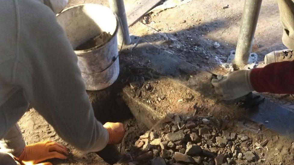 Renovators find objects hidden under a chimney at Auschwitz