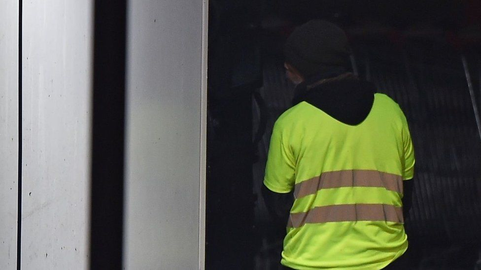 A man wearing a yellow vest and reportedly wielding a grenade, which could be a tear gas, stands as police carry out an intervention at the car wash station of the Espace Anjou shopping centre in Angers, western France,