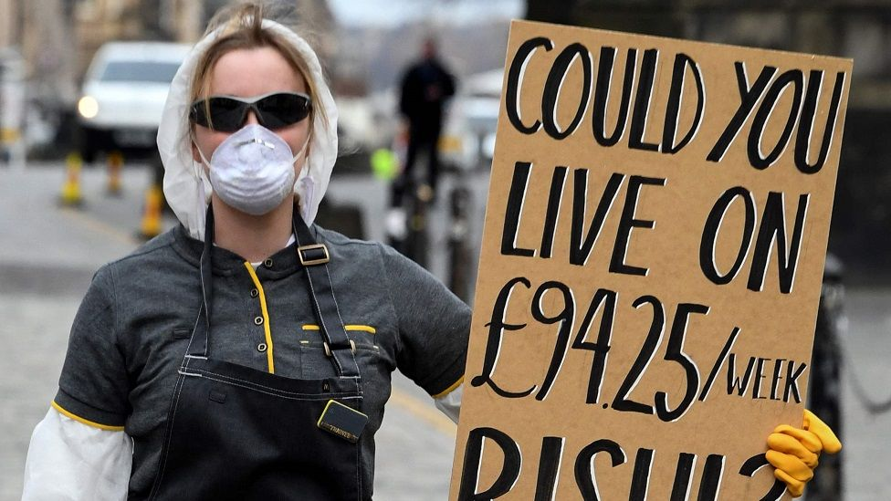 A woman wearing a protective face mask and gloves holds a placard complaining about the lack of support for the self-employed and zero hours contract workers, on the Royal Mile in Edinburgh in Scotland on March 23