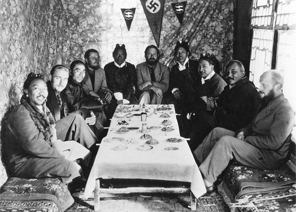 chaefer, Ernst *1912-1992+Zoologe, D Leiter der SS-Tibetexpedition,'SS-Wissenschaftler' 1934 zum Sturmführer ehrenhalber ernannt.- mit Tibetern bei einem Gastmahl in Lhasa, 1939.In der Mitte E.Schaefer, daneben (l) Tsarong Dzasa, 2.v. links Bruno Beger, 4.v.l. Edmund Geer (beide Anthropologen), rechts Karl Wienert neben dem Tibetaner Möndro.