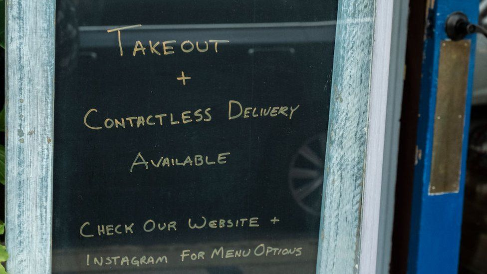 A sign outside a restaurant in New Jersey offering takeaway and contactless delivery services during the coronavirus lockdown