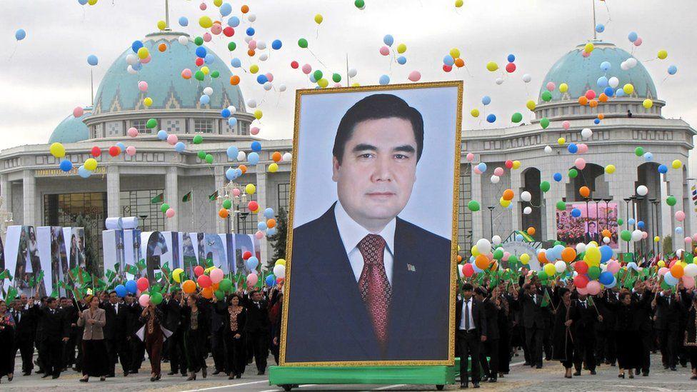People carry a picture of Turkmen President Kurbanguly Berdymukhammedov to mark Turkmenistan's Independence Day in Ashgabat on 27 October 2009
