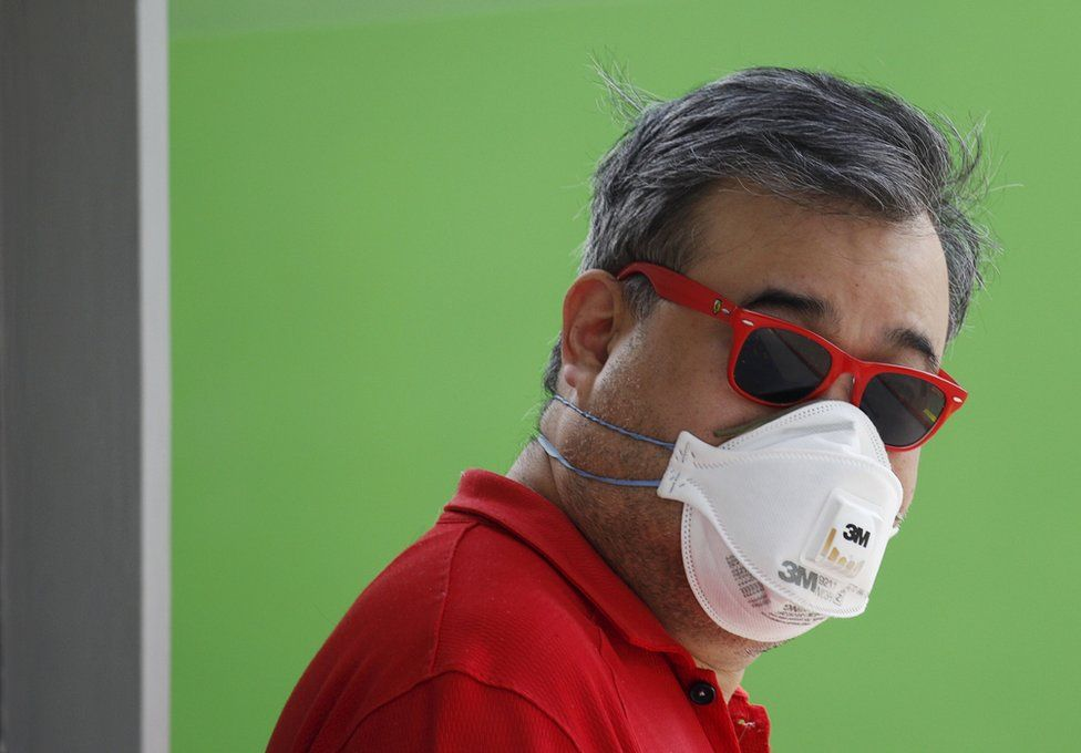 A man wearing a mask for protection against the haze as he waits at a polling station during the general election in Singapore 11 September 2015.