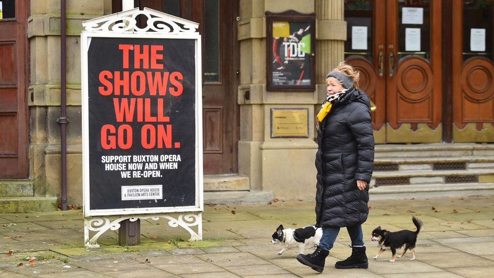 """Woman walking past a theatre sign saying """"The shows will go on"""""""