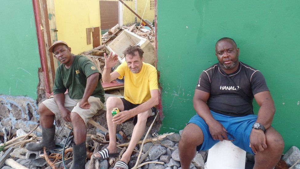 Wyfee Joules and his friends sit on the steps of what was once his bar.