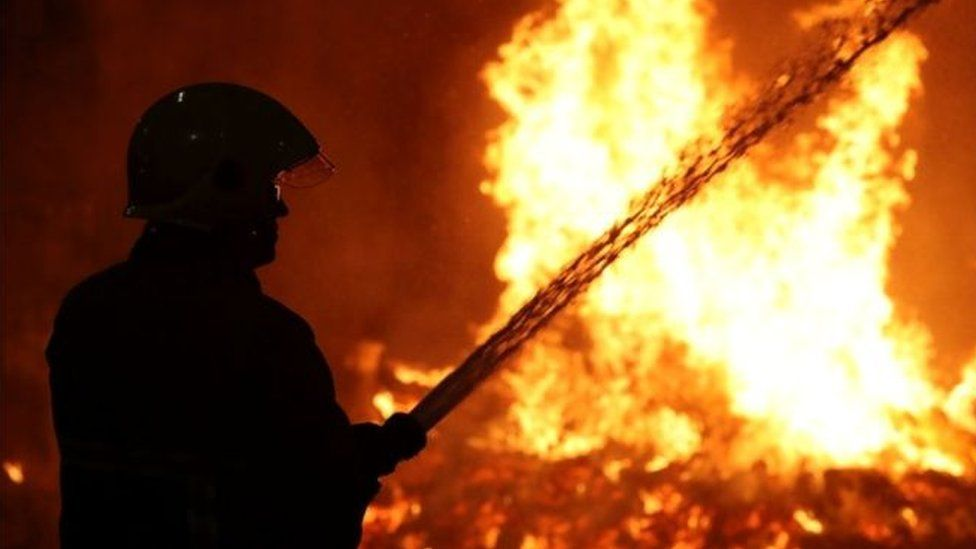 A firefighter dampens down surrounding buildings on Cluan Place, east Belfast