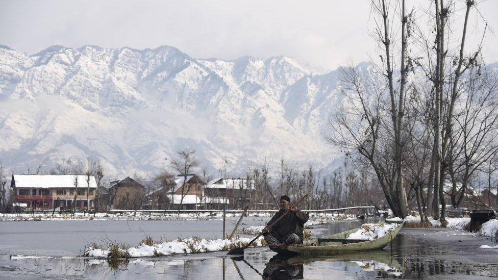 A Kashmiri boatman rows his boat on Dal Lake after fresh snowfall in Srinagar.