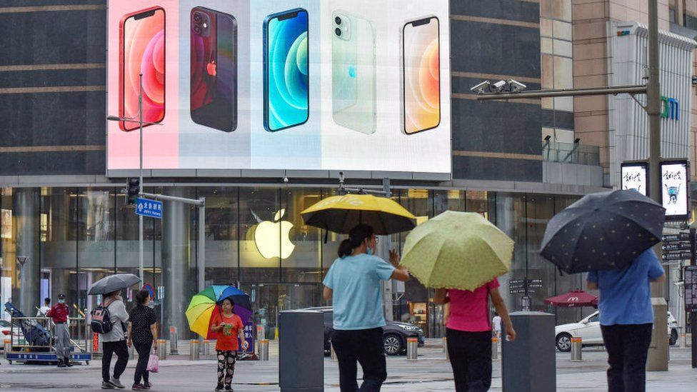 iPhone smartphones seen displayed on a large screen outside the Apple store on Wangfujing Street in Beijing.