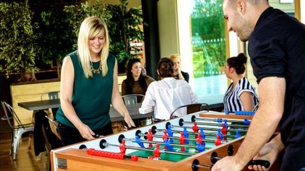 People playing table football at Moneypenny office