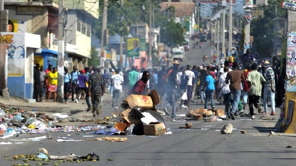 Demonstrators place barricades on the street during a march in Port-au-Prince on 24 November, 2015.