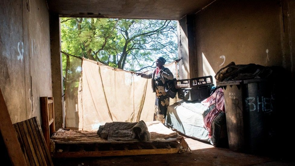 An unidentified woman stands in a room containing a mattress and other minimal essentials in the derelict San Jose building in Johannesburg, South Africa
