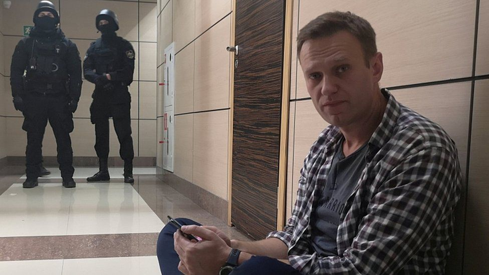 Alexei Navalny sits on the floor outside the office of his Anti-Corruption Foundation during a police raid in Moscow, 26 December 2019