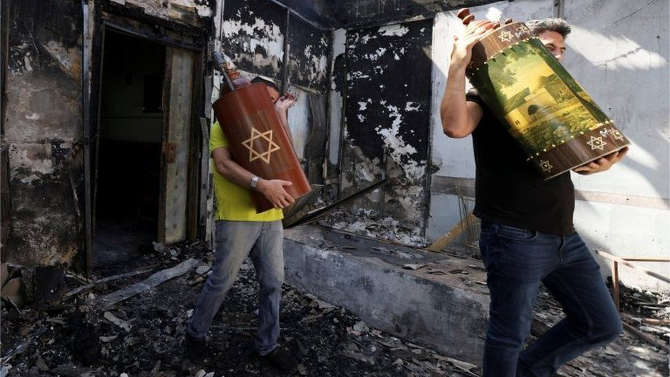 Torah scrolls, Jewish holy scriptures, are removed from a synagogue in the city of Lod, Israel (May 12, 2021)