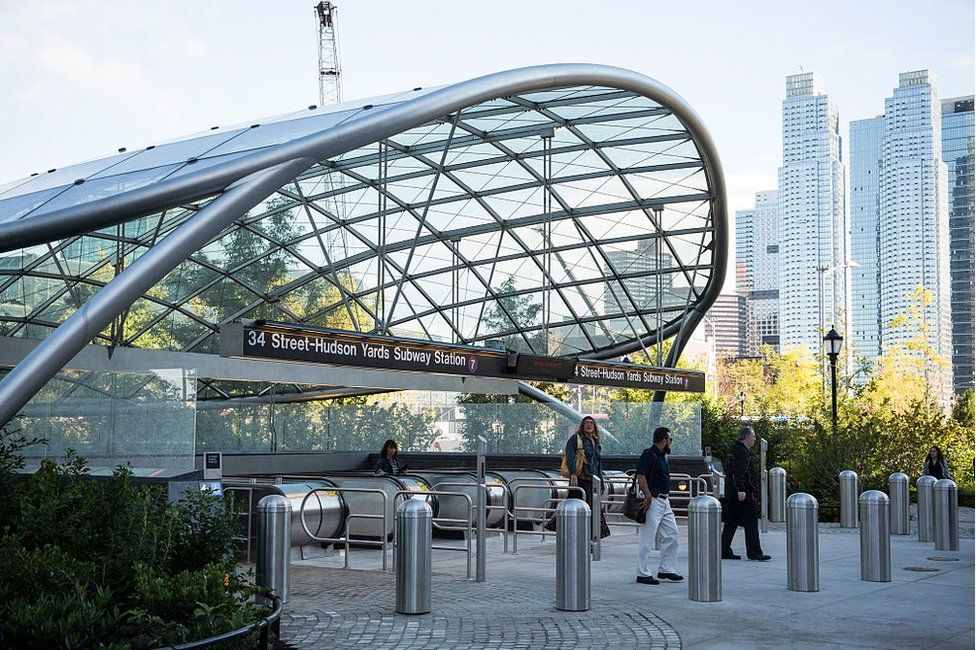 "The entrance to the ""34th Street, Hudson Yards"" subway station with skyscrapers in the distance"