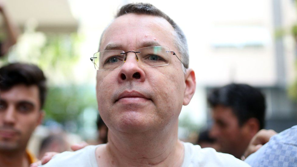 Pastor Andrew Craig Brunson is escorted by Turkish plainclothes police officers as he arrives at his house in Izmir, Turkey, 25 July 2018