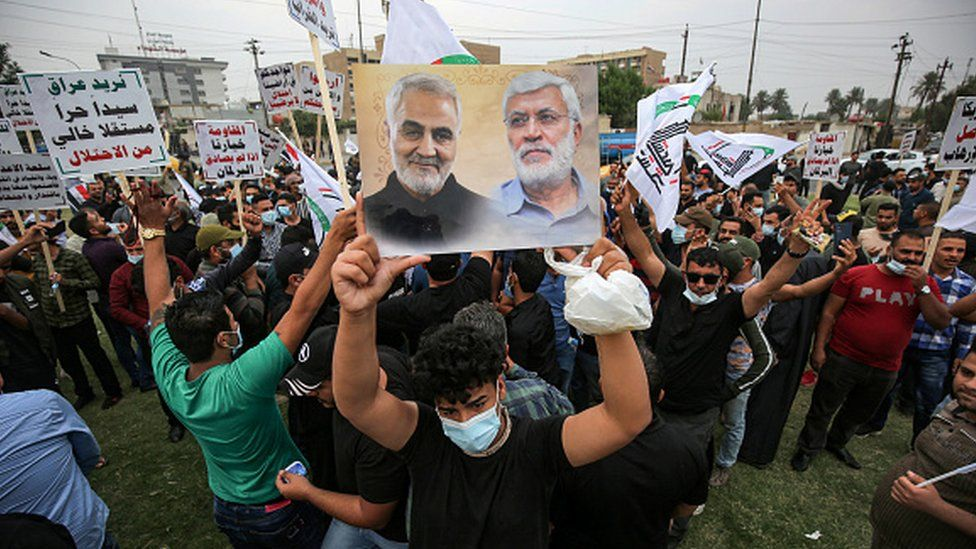 A protesters holds a picture showing the face of slain Iranian commander Qasem Soleimani