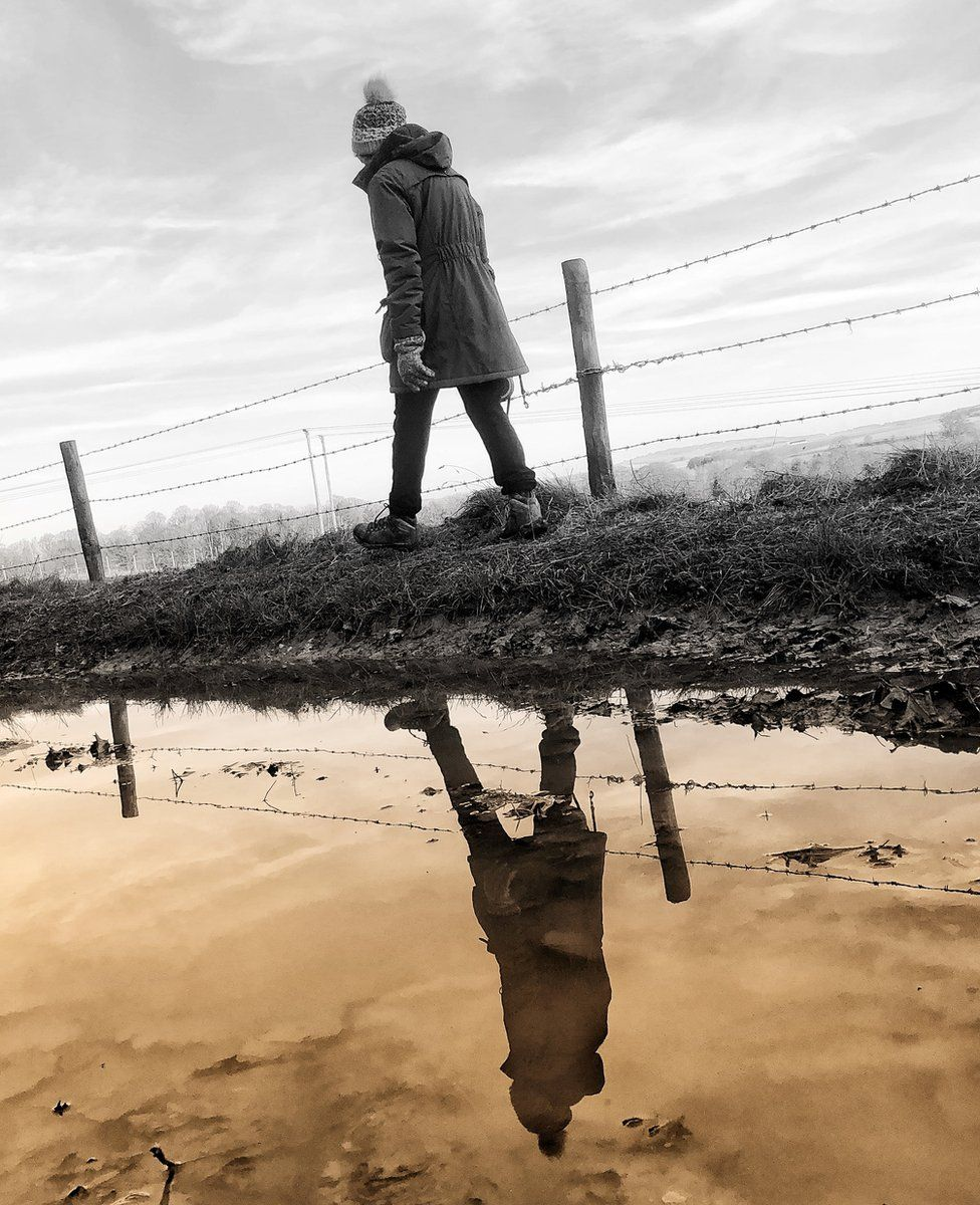 Woman passing a puddle