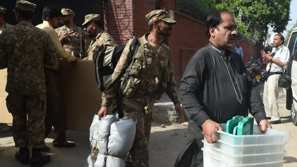 Pakistani soldiers help a polling officer carry election materials in Lahore (16 September 2017)