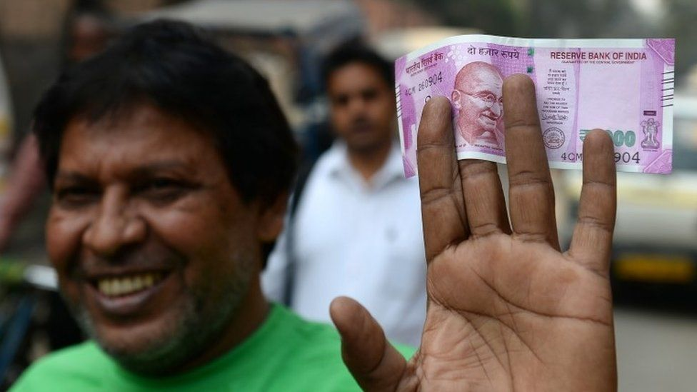 An Indian man displays a new 2000 rupee note after exchanging his old 500 and 1000 rupee notes at a bank in New Delhi on November 10, 2016.