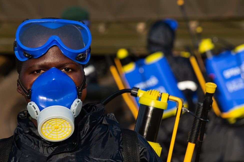 A soldier prepares equipment to spray crops