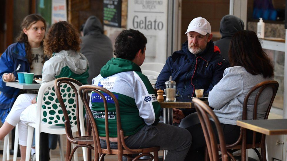 People sit at a beachside cafe in Bronte, Sydney on the first day of the city's reopening