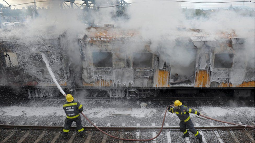 Firefighters douse a train carriage to put out a fire