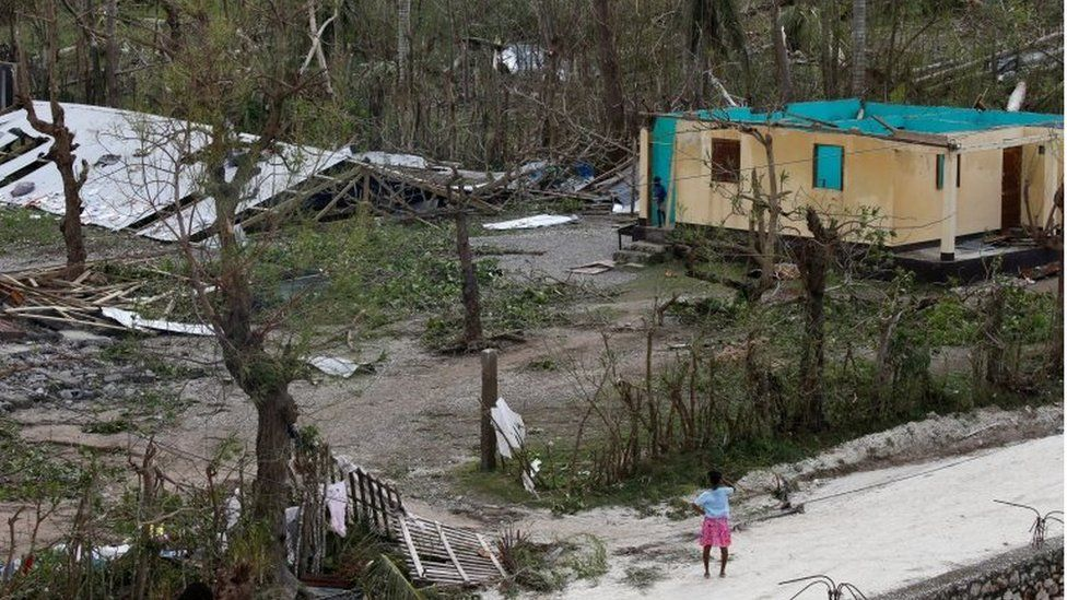 A woman stands in front of a destroyed house after Hurricane Matthew passes Jeremie, Haiti, on 5 October 2016.