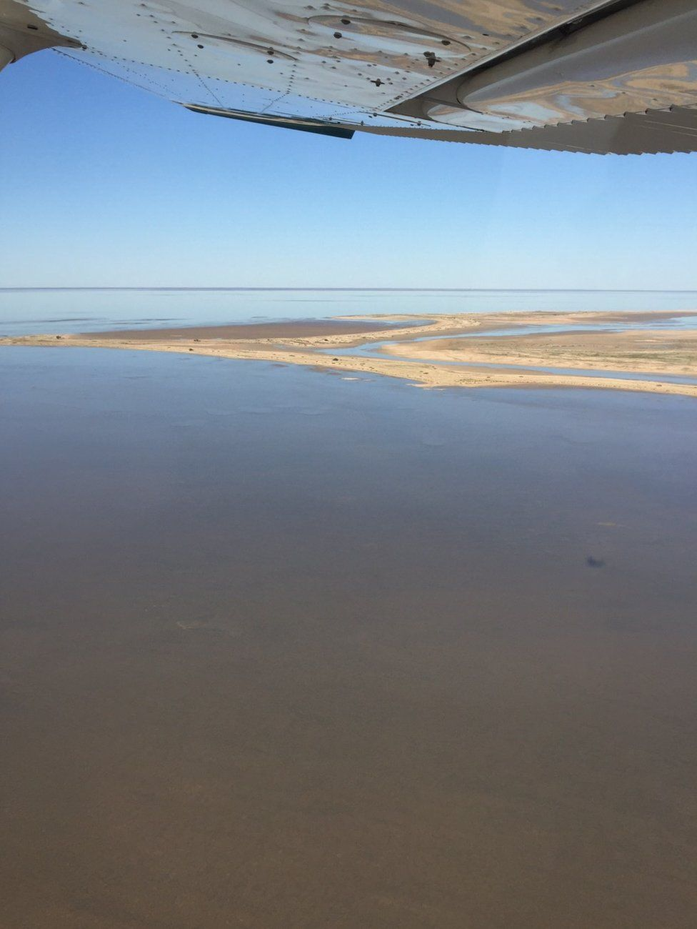 Sand banks peak above the water in Lake Eyre